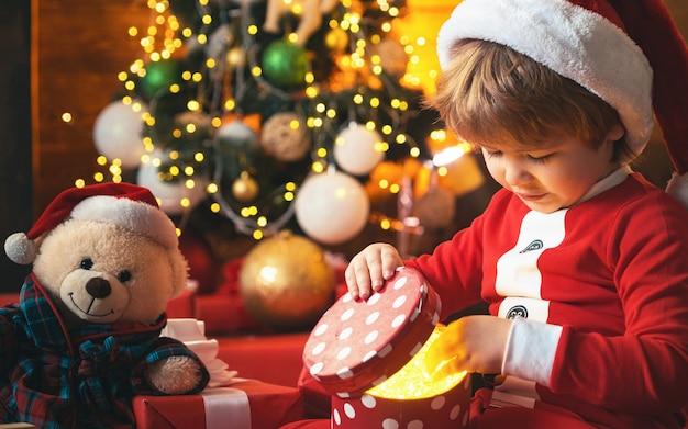 Boże narodzenie dziecko. szczęśliwy mały uśmiechnięty chłopiec z świątecznym pudełkiem. szczęśliwe dziecko trzyma czerwone pudełko