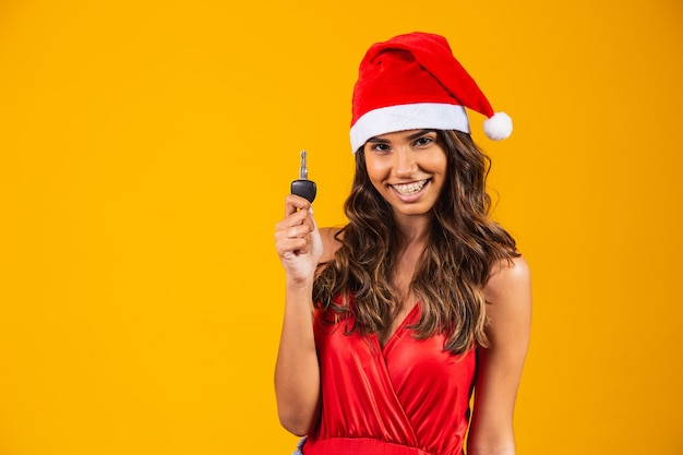 Boże narodzenie dziewczyna w santa hat trzymając kluczyki do samochodu. odosobniony.