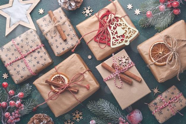 Boże narodzenie gałęzie jodły, bombki, pudełko na prezenty, drewniane płatki śniegu i gwiazdy na zielonym tle kamienia betonu na życzenia świąteczne. widok z góry z miejsca na kopię. kartkę z życzeniami świątecznymi.