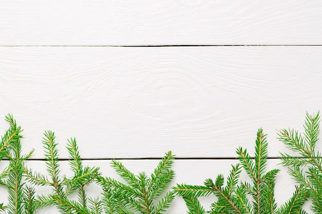 Boże narodzenie gałęzie jodły na białej drewnianej desce