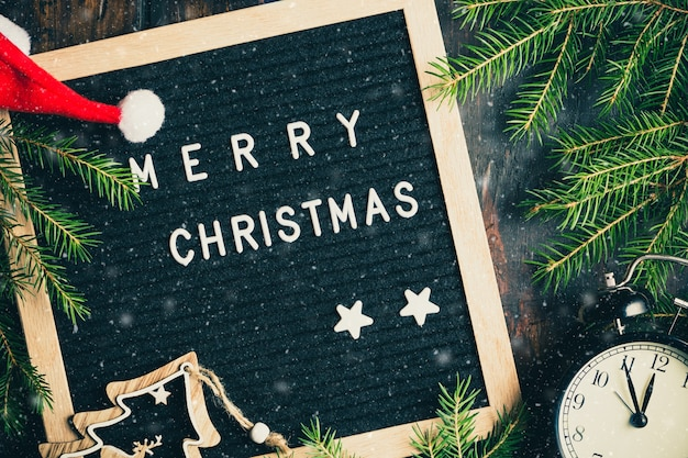 Boże narodzenie gałęzie jodły z zegarem i pudełka na prezenty w pobliżu tablicy ze słowami wesołych świąt.