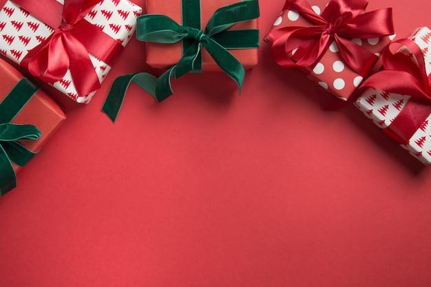 Boże narodzenie granica świątecznych prezentów na czerwonym tle. drugi dzień świąt kartka z życzeniami.