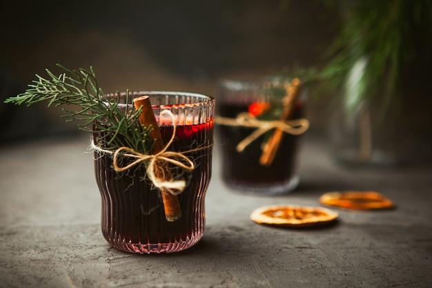 Boże narodzenie grzane czerwone wino z aromatycznymi przyprawami i owocami cytrusowymi na czarnej powierzchni, zbliżenie. tradycyjny gorący napój w okresie świątecznym