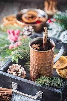 Boże narodzenie grzane czerwone wino z przyprawami i owocami na drewnianym stole w stylu rustykalnym. tradycyjny gorący napój w okresie bożego narodzenia