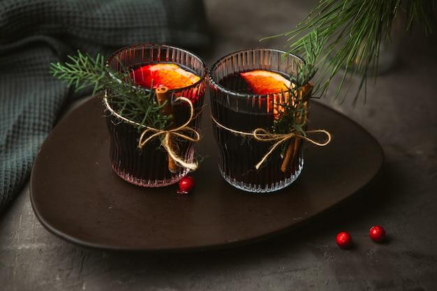 Boże narodzenie grzane wino czerwone z aromatycznymi przyprawami i owocami cytrusowymi na talerzu, zbliżenie. tradycyjny gorący napój w okresie świątecznym