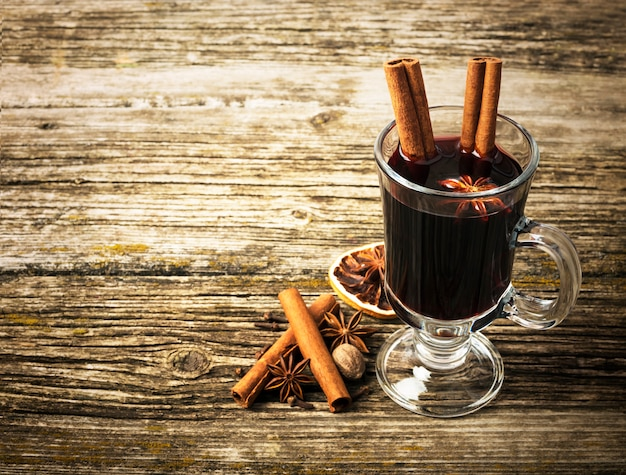 Boże narodzenie grzane wino w szklanej filiżance na drewnianym stole.
