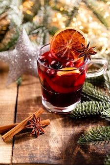 Boże narodzenie grzane wino z przyprawami na drewnianym stole w stylu rustykalnym.