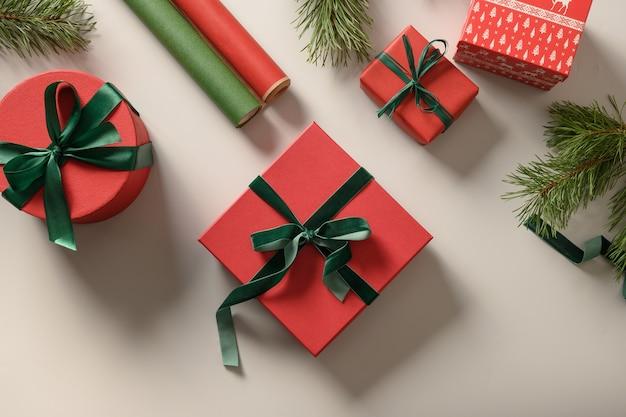 Boże narodzenie hodowane i zielone pudełka prezentowe, rolki papieru na szaro. przygotowanie i opakowanie prezentu na święta. widok z góry