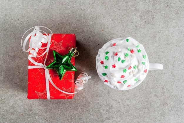 Boże narodzenie i. jedno świąteczne pudełko z czerwonego papieru i kubek na kawę lub gorącą czekoladę, z bitą śmietaną i dekoracją słodkich gwiazd, na szarym kamiennym stole, widok z góry