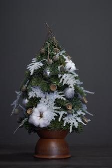 Boże narodzenie i kompozycja. choinka wykonana z gałęzi jodłowych i ozdobiona naturalnymi materiałami i kulkami w glinianym garnku