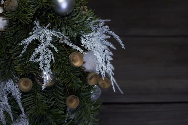 Boże narodzenie i kompozycja. szczegóły zbliżenie choinka wykonana z gałęzi jodły i ozdobiona naturalnymi materiałami i kulkami na ciemności