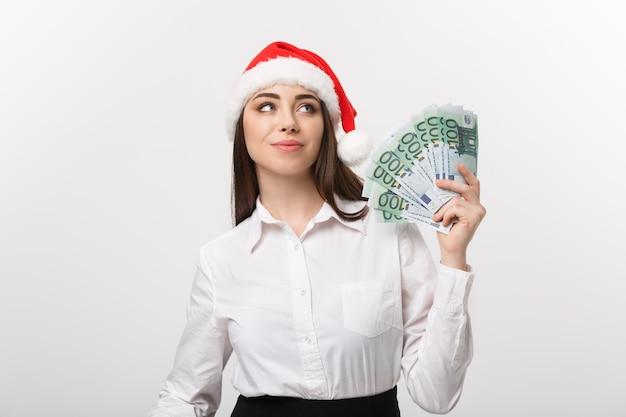 Boże narodzenie i koncepcja finansowa młoda kobieta pewnie biznesu pokazuje pieniądze przed nią z radosną buźkę
