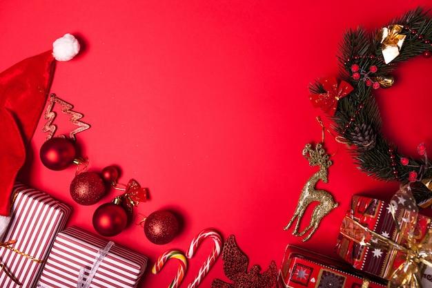 Boże narodzenie i nowy rok czerwone tło zdobione pudełka, kapelusz santa i zabawki