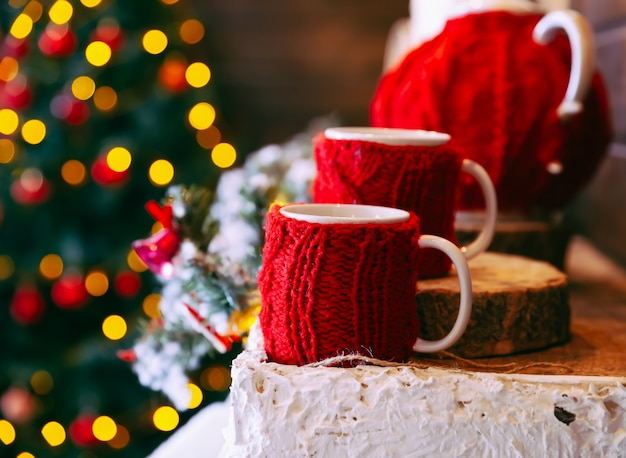 Boże narodzenie i nowy rok. dwa czerwone kubki w boże narodzenie ozdobione domu światłem i drzewem nowego roku