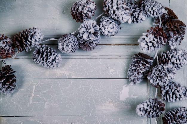 Boże narodzenie i nowy rok skład - szyszki na tle drewnianych białych drzwi. stare teksturowane tło z szyszek świerkowych i sosnowych ze spotkaniem xmas i szczęśliwego nowego roku. skopiuj miejsce na stronę