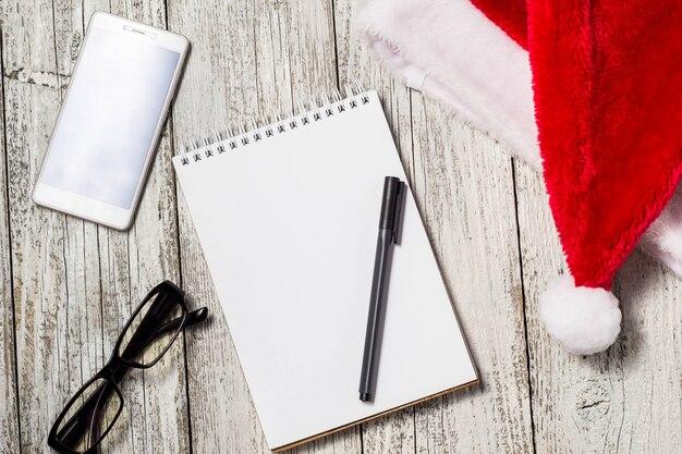 Boże narodzenie i nowy rok tło z smartphone, czerwony kapelusz santa, okulary, notatnik i długopis dla swoich życzeń