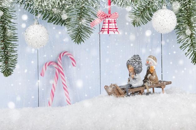 Boże narodzenie i nowy rok tło z uśmiechniętymi figurkami na saniach, ozdób choinkowych i cukierków