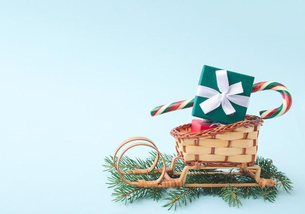 Boże narodzenie i nowy rok w tle. sanie świętego mikołaja z pudełkiem prezentowym i słodyczami na gałęziach jodły na jasnoniebieskim tle. skopiuj miejsce