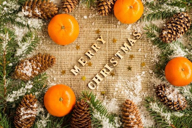 Boże narodzenie i nowy rok w tle w rosyjskich tradycjach świątecznych. dojrzałe pomarańczowe mandarynki, szyszki świerkowe i ośnieżone gałęzie świerka.