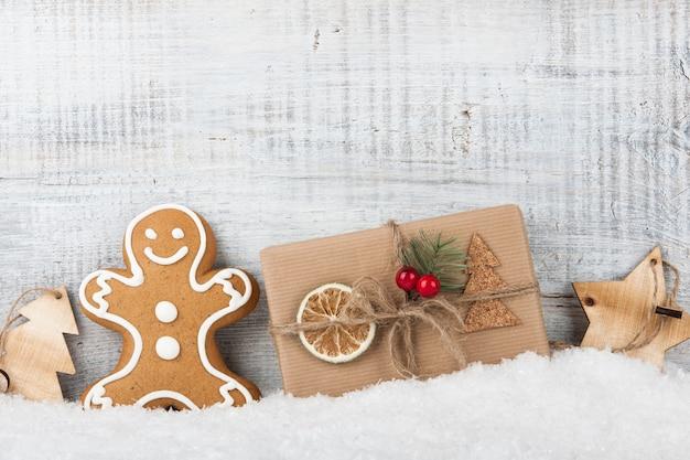 Boże narodzenie i nowy rok z pudełkiem prezentowym, piernikami świątecznymi i ozdobami świątecznymi na śniegu