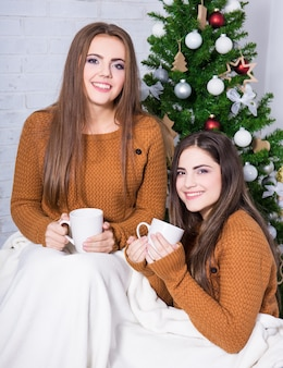 Boże narodzenie i przyjaźń dziewczyny rozmawiają i piją kawę lub herbatę w pobliżu choinki