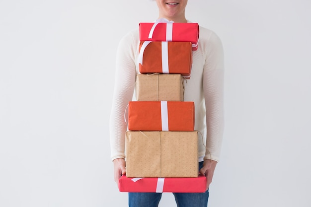 Boże narodzenie i święta koncepcja bliska mężczyzny trzymającego stos pudełek prezentowych na białym tle