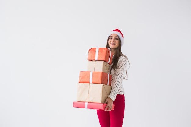 Boże narodzenie i święta koncepcja - kobieta w santa hat z wieloma prezentami na białym tle z miejscem na kopię