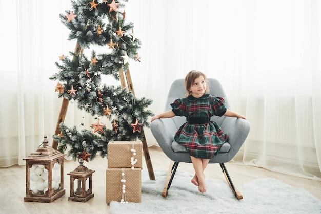 Boże narodzenie i święta koncepcja. śliczna mała dziewczynka siedzi na krześle obok drabiny ozdobionej gwiazdami i pudełkami prezentowymi na podłodze.