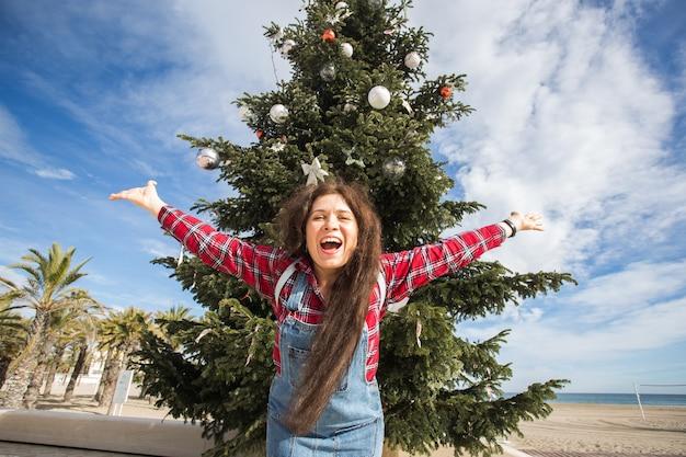 Boże narodzenie i wakacje koncepcja - szczęśliwa kobieta skacząca na choinkę.
