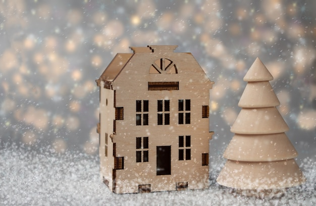Boże narodzenie ilustracja. zabawkowy drewniany dom z choinką i padający śnieg na rozmytym tle