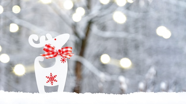 Boże narodzenie jelenie w śniegu, na tle niewyraźne zima z bokeh świateł. kartka świąteczna z miejscem na tekst.