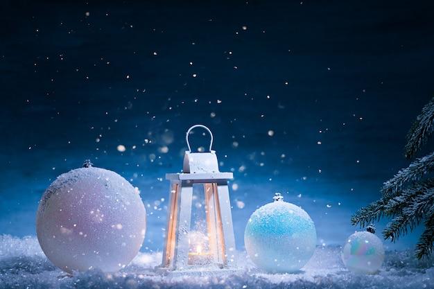 Boże narodzenie jest tutaj. minimalna kreatywna kompozycja z białą latarnią i bombkami
