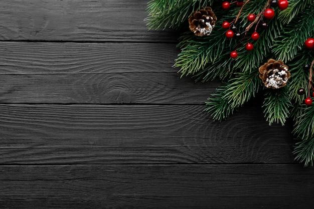Boże narodzenie jodła na czarnym tle drewnianych, kopia przestrzeń. szeroki obraz