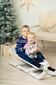 Boże narodzenie już tu jest. dwóch braci na sankach z świątecznym pudełkiem. mały śliczny chłopiec otrzymał prezenty świąteczne. pudełko na prezent dla dzieci. świętować boże narodzenie. aktywność zimowa