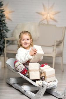 Boże narodzenie już tu jest. dziewczyna na sankach z świątecznym pudełkiem. mała śliczna dziewczyna otrzymała prezenty świąteczne. pudełko na prezent dla dzieci. świętować boże narodzenie. aktywność zimowa