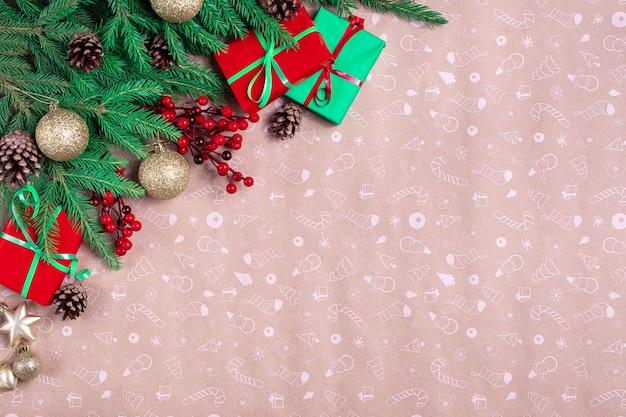 Boże narodzenie kącik z zielonymi gałązkami jodły, dekoracjami i prezentami świątecznymi na tle papieru artystycznego.