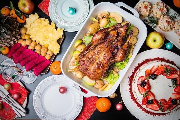 Boże Narodzenie Kaczka Z Jabłkami I Ziołami Na Białej Patelni Na Drewnianym Tle, Widok Z Góry Premium Zdjęcia