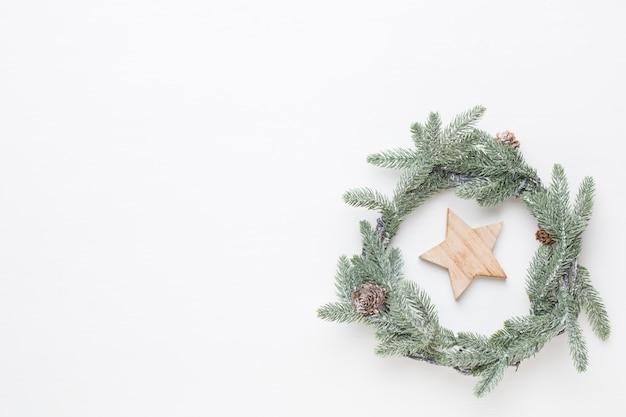 Boże narodzenie kartkę z życzeniami. dekoracja wieniec na białym tle drewnianych. koncepcja nowego roku. skopiuj miejsce. leżał na płasko. widok z góry.