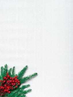 Boże narodzenie kartkę z życzeniami. gałąź zielonych igieł i holly berry na białym papierze falistym. zdjęcie pionowe