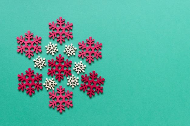 Boże narodzenie kartkę z życzeniami z czerwonymi białymi drewnianymi płatkami śniegu na zielonym tle. zdjęcie z pustą przestrzenią kopii.