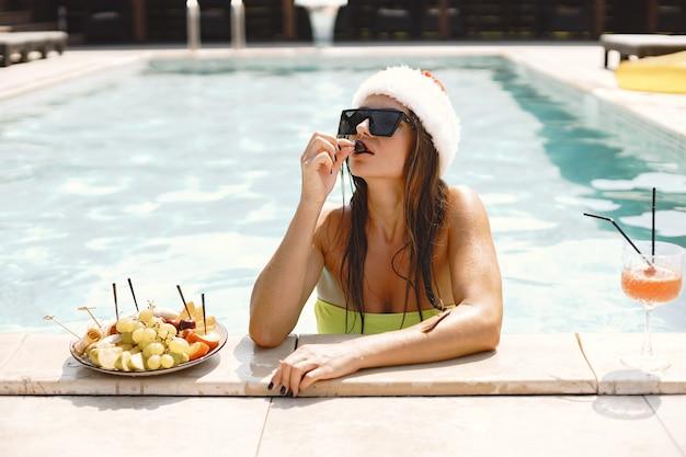 Boże narodzenie kobieta relaks przy basenie. zabawna dziewczyna świętuje boże narodzenie w ośrodku. z koktajlem i owocami.