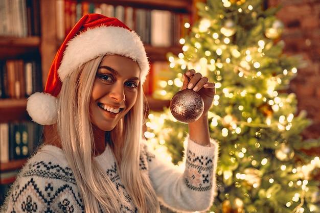 Boże narodzenie kobieta. wesołych świąt i wesołych świąt. szczęśliwa dziewczyna udekoruje choinkę w pomieszczeniu - magiczny świąteczny bokeh. ranek przed świętami. portret kochający blondynka z bliska