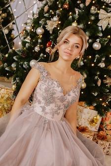 Boże narodzenie, koncepcja ferii zimowych. piękna kobieta w długiej sukni wieczorowej pozowanie w luksusowych apartamentach urządzonych na boże narodzenie. piękno, moda.