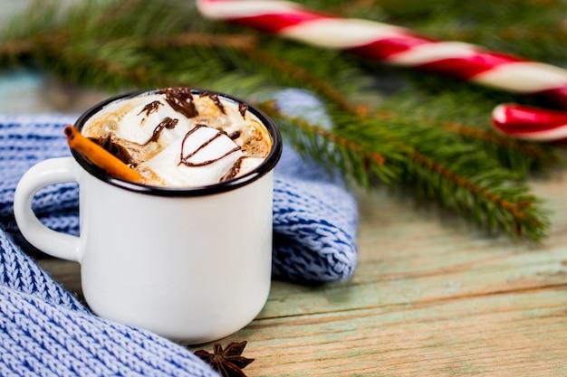 Boże narodzenie koncepcja, gorąca czekolada lub kakao z piankami i przyprawami, prezenty świąteczne, laski, gałęzi choinki i szyszki sosnowe, na starym rustykalnym drewnianym stole.