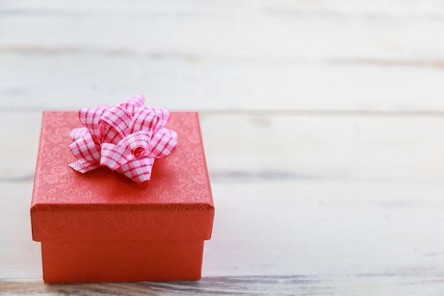 Boże narodzenie, koncepcja strony nowego roku. zbliżenie piękne czerwone pudełko na biały drewniany stół.