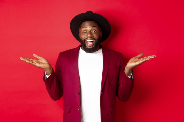 Boże narodzenie koncepcja zakupy i ludzie. przystojny afroamerykanin uśmiechnięty, rozłożony ręce na boki, pokazujący oferty promocyjne na miejscu, czerwone tło.
