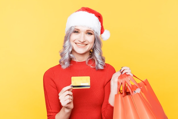 Boże narodzenie koncepcja zakupy online. boże narodzenie dziewczyna trzyma kartę kredytową i duże torby.