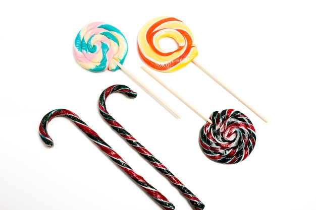 Boże narodzenie laski i kolorowe okrągłe słodycze na białym tle