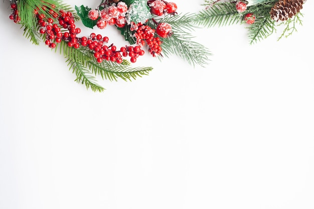 Boże narodzenie leżało na płasko, świerkowe gałązki, czerwone jagody i szyszki, posypane śniegiem, kopia przestrzeń