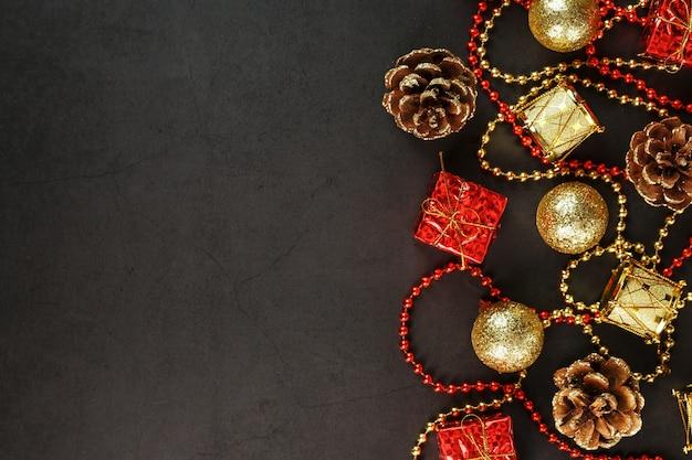 Boże narodzenie lub nowy rok ciemne tło z czerwonymi i złotymi dekoracjami na choinkę z wolnego miejsca. widok z góry. świąteczny nastrój.